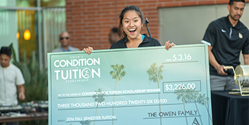 Winner of Condition for Tuition holding a large check
