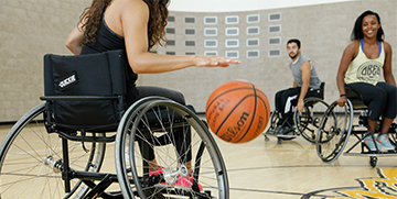People in wheelchairs playing basketball