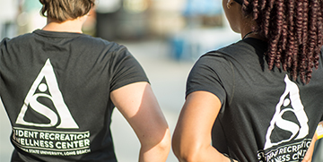 Two females wearing Student Recreation and Wellness Center shirts